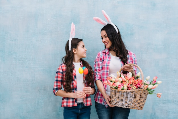 Mother holding tulips basket looking at girl holding easter eggs in hand against blue background