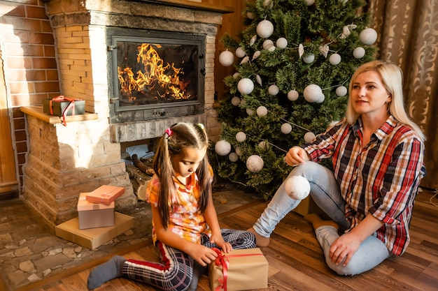 Мать держит маленькую дочь у елки праздничным вечером в деревенском деревянном доме, новый год, зимнее время