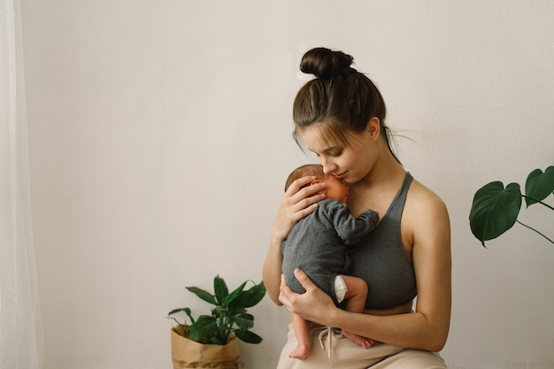 Мать держит и обнимает своего новорожденного сына дома счастливым младенцем и мамой