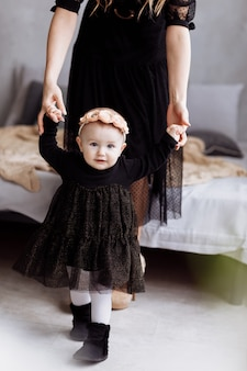 Мать держит руки дочери наслаждаться время вместе дома. смотреть вниз по ногам. мама, детский день. концепция праздника молодой семьи и забота о любви и поддержка следующего поколения.