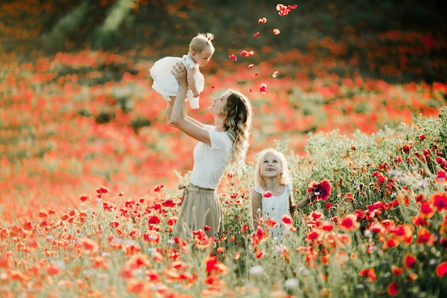 Mother holds her baby at height, her elder daughter smiles on the poppy field