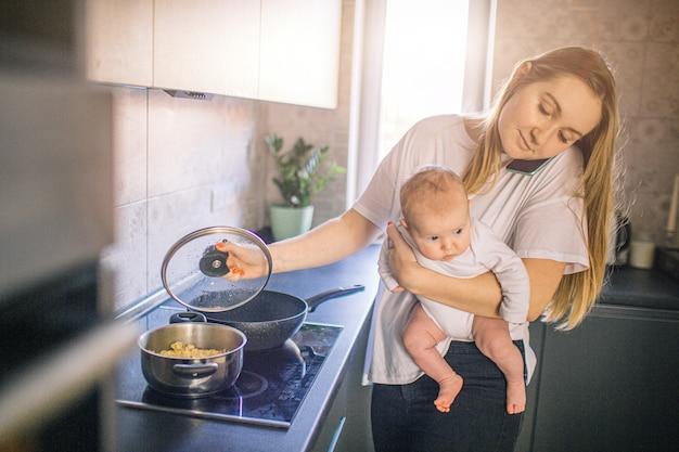 母親は赤ちゃんを両腕に抱えています。そして、台所で料理をします。ママは電話で話し、とても忙しい。多機能性のコンセプト。