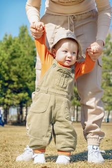 Mother holds her baby's hands in city park as the child learns to walk