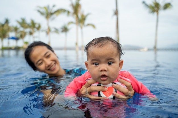Mother holds her baby while learning to swim