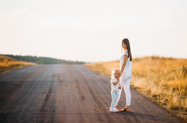 母は彼女の小さな娘を手で持って、彼らは夏の日没の光線の中で道路に立っています