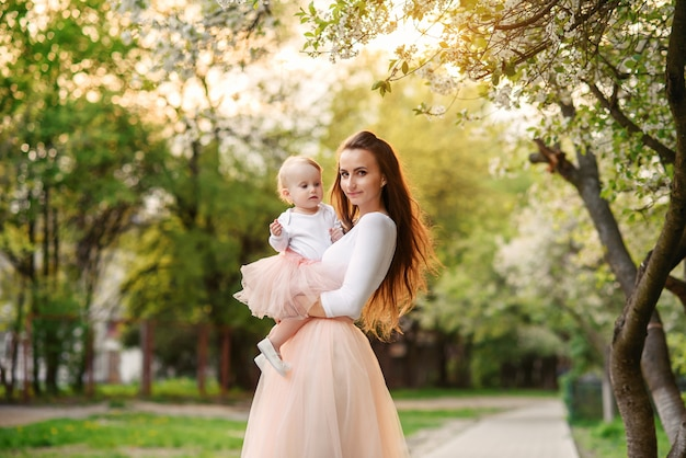 Mother holds her little daughter in her arms among blooming trees. mom and her little baby weared pink family look dress.