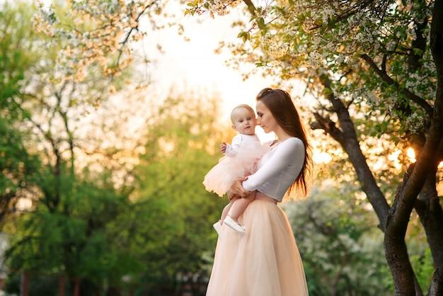 Мать держит ее маленькую дочь на руках среди цветущих деревьев. мама и ее маленький ребенок носили розовое семейное платье.