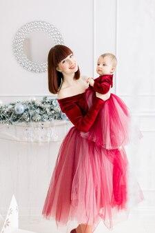 어머니는 손에 그녀의 어린 소녀를 보유하고 크리스마스 장식과 함께 라이트 룸에서 포즈