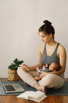 Мать держит своего новорожденного сына и работает за компьютером дома