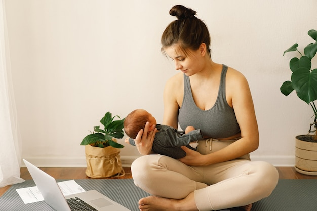 Mother holds her newborn baby son and works at the computer at home