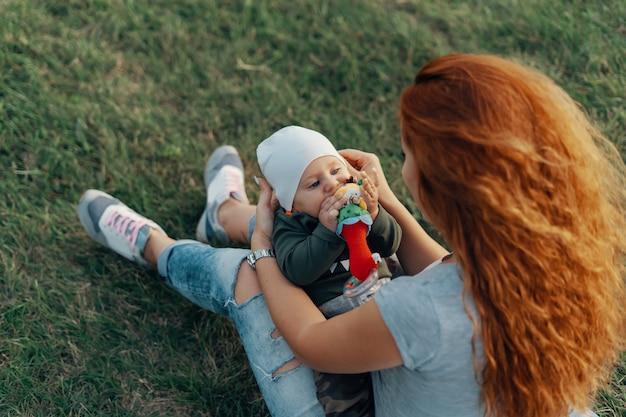 Мать держит сына на коленях, играя на траве