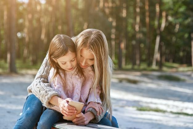 Мать держит смеющуюся маленькую девочку и показывает ей смартфон. приятная семейная прогулка в лесу