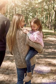 Мать держит на руках смеющуюся двухлетнюю дочь. приятная семейная прогулка в лесу