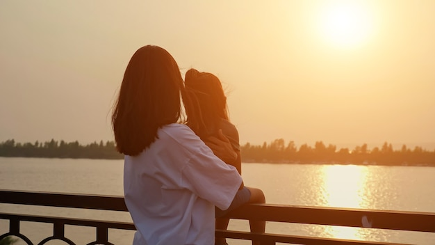 Mother holds little girl on railing on waterfront at sunset