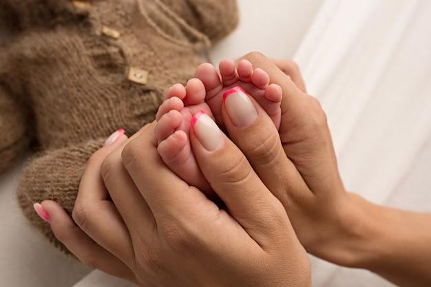 Мать держит босые ноги новорожденного. крошечные ножки в руке женщины. уютное утро дома. фото высокого качества
