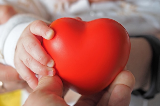 A mother holds a red heart with a small child in her hands. concept of maternal love, child health