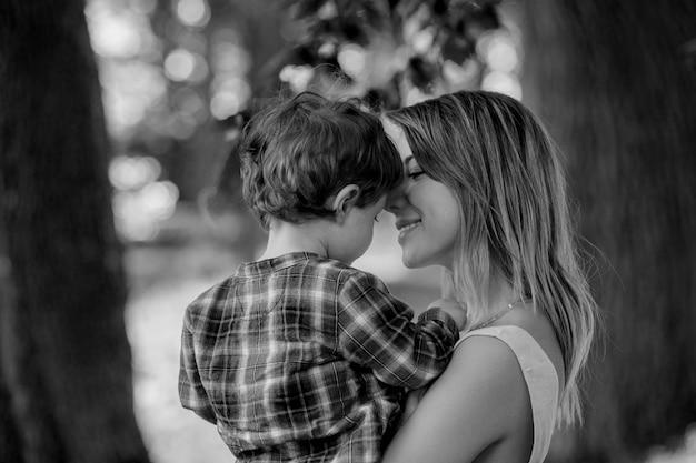 Мать держит сына на руках на открытом воздухе