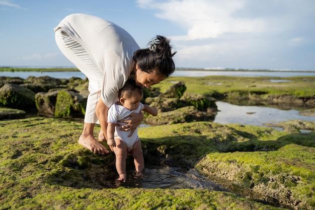 赤ちゃんの足が砂浜に触れたときに母親が赤ちゃんを抱きしめる