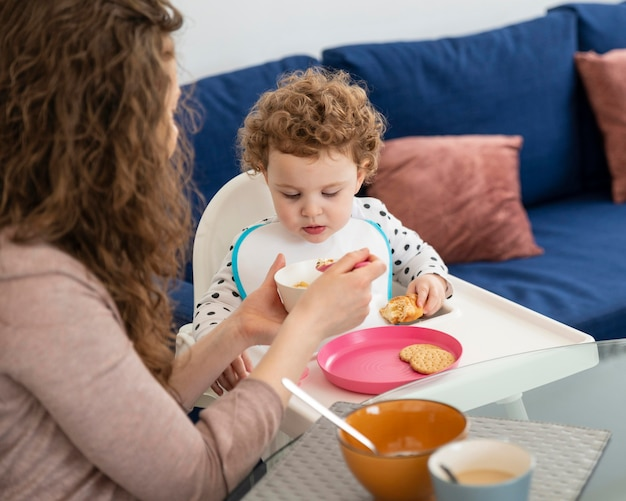 Mother at home with child having lunch