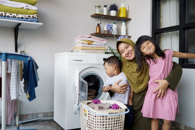 Mother a housewife with a baby engaged in laundry with washing machine