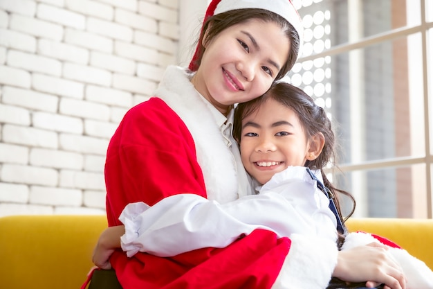 Mother hug daughter in santa hats celebrate christmas at home.