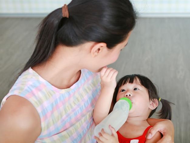 母親は抱擁するかわいいアジアの子供の女の子は、瓶から飲む