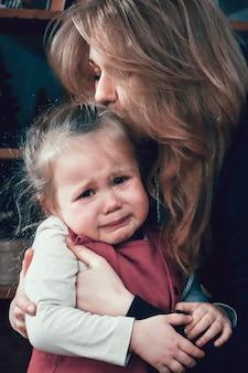 泣いている赤ちゃんを抱き締める母親。家族ケアのコンセプト。