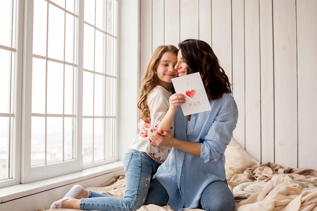 Mother hugging cute daughter with greeting card