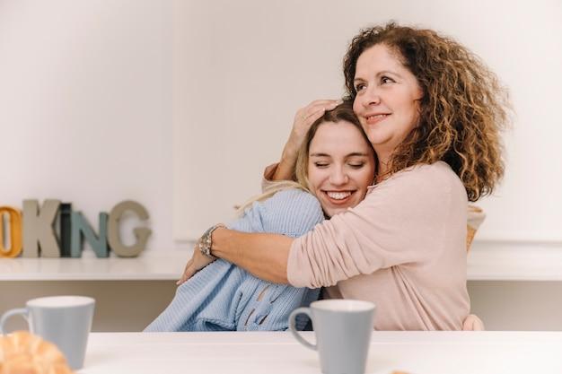 Мать обнимает дочь во время завтрака