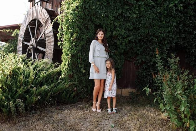 Мать обнимает дочь любит гулять на свежем воздухе и смотреть на природу. молодая семья проводит время вместе в отпуске, на открытом воздухе.