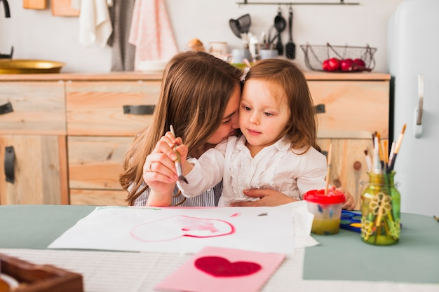 Мать обнимает дочь, пока она рисует сердце