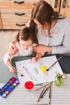 Mother hugging daughter while she painting