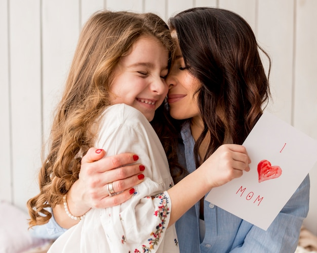 Mother hugging daughter with greeting card