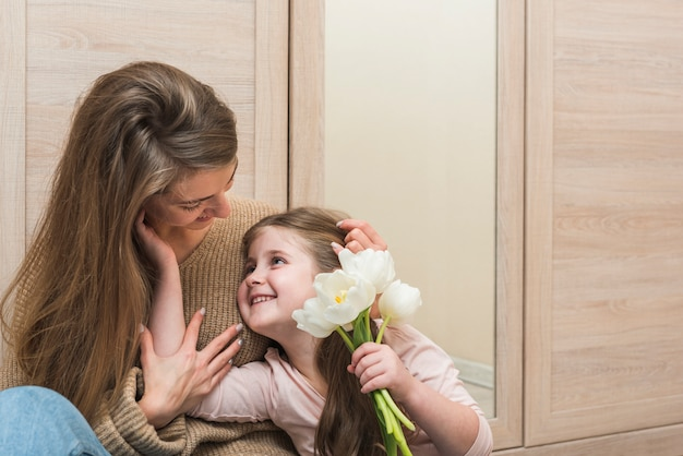 Mother hugging daughter with tulip flowers