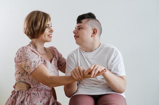 大脳性麻痺の車椅子で障害のある少年を抱き締める母親