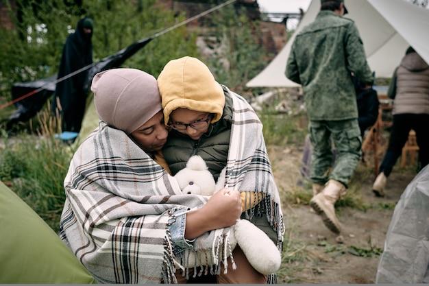 겁 먹은 아이를 껴안고 있는 어머니 프리미엄 사진