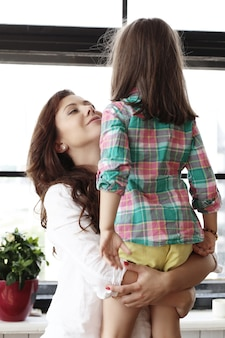 Мать обнимает девочку дома