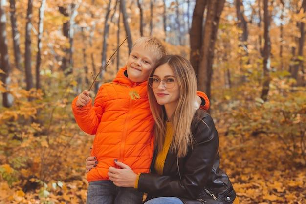 秋の公園の秋の季節とひとり親の概念の散歩中に彼女の子供を抱き締める母