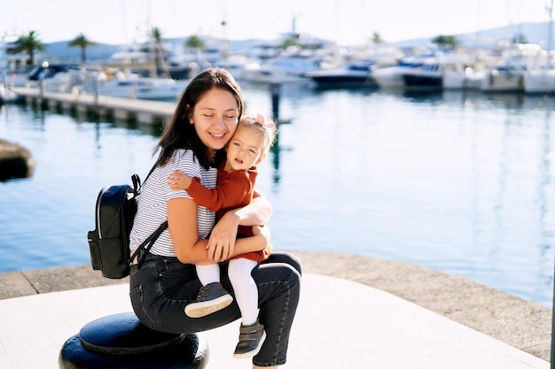 Mother hugging her daghter on a walk at a boat marina in montenegro.