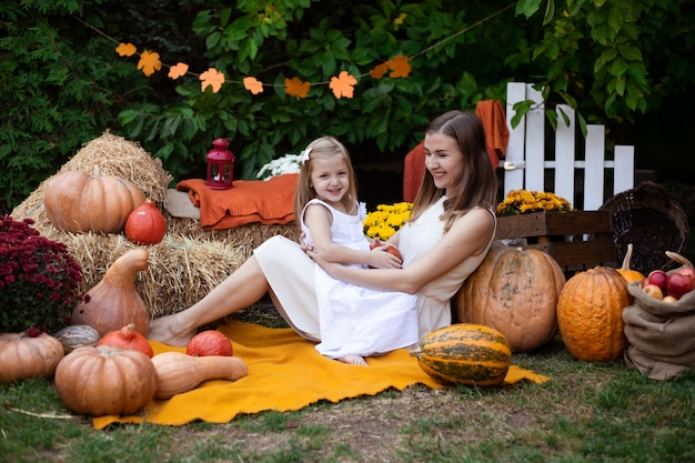 Mother hugging her daughter in autumn background with pumpkins
