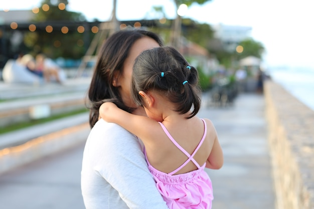 Mother hugging her daughter child girl on sea background in the evening