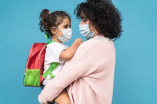 코로나바이러스 발병 동안 학교로 돌아가는 딸을 안고 있는 어머니 - 여성의 얼굴에 초점