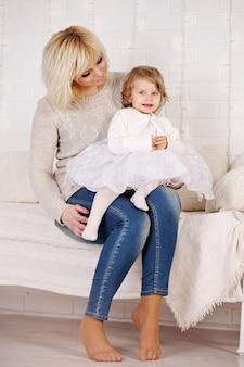 白いベッドに座っている娘を抱き締める母