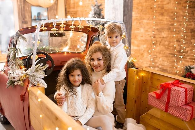 赤い車のピックアップトレーラーのクリスマスツリーとライトの近くで彼女の小さな子供たちを抱き締める母