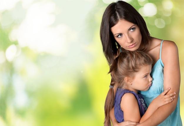 ぼやけた緑の背景に彼女の小さな娘を抱き締める母