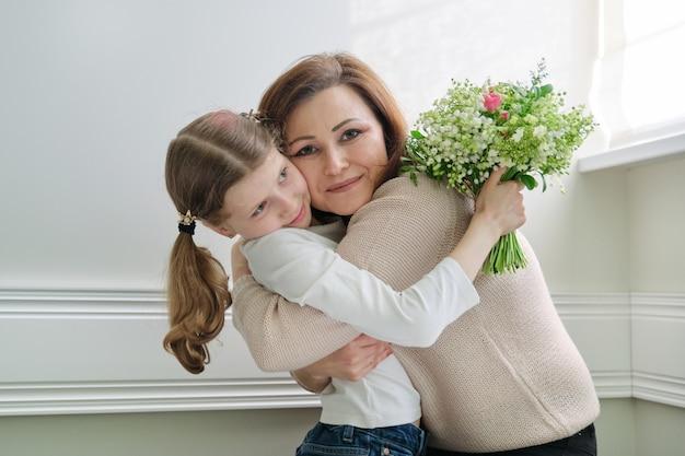 美しい春の花の花束で彼女の小さな娘を抱き締める母