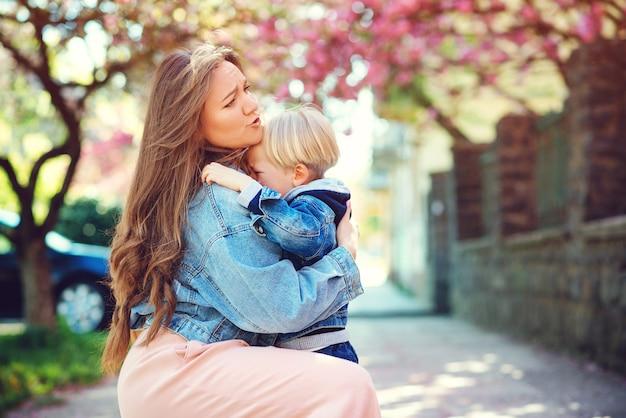 悲しい息子を屋外に抱いて母。通りで泣いている幼児の少年。母性、家族、ライフスタイル。