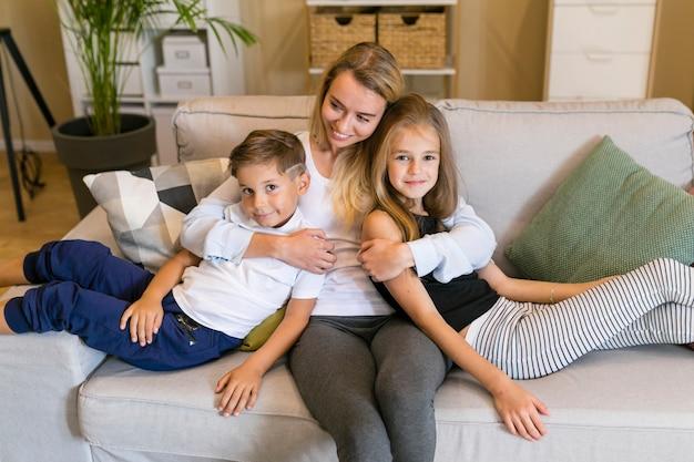 Мать обнимает сына и дочь