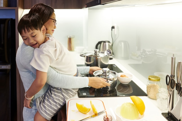 Мать обнимает сына и ставит кастрюлю с водой на плиту