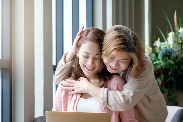 Mother hugging and teasing with her daughter while working on laptop at home, happy family concept.